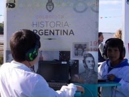 Dos niños en el Parque Pakapaka utilizan las netbooks y auricularse del stand Colección Historia argentina.