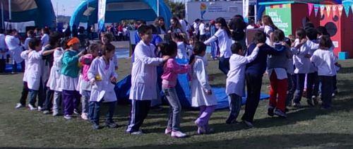 Chicos y chicas des escuale primaria, con guardapolvo blanco, jugando al aire libre. En color.