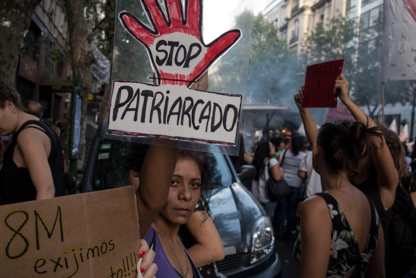 Fotografía color tomada durante una marcha del 8M, Día Internacional de la Mujer. En la calle, una mujer sostiene un cartel con el texto: Stop patriarcado.