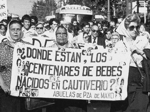 Fotografía de una marcha. En primer plano un cartel en el que se lee: ¿Dónde están los centenares de bebes nacidos en cautiverio.