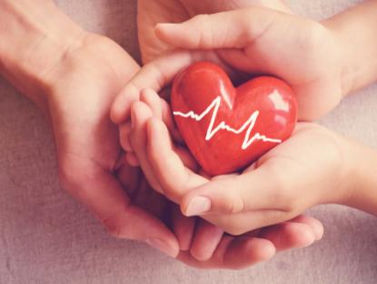 Dos manos entrecruzadas sosteniendo un objeto rojo con forma de corazón. El objeto tiene dibujada en blanco la línea de un electrocardiograma.