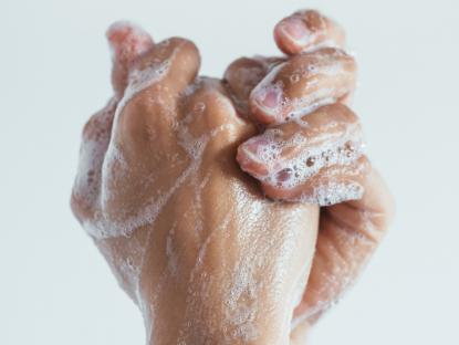 Dos manos entrecruzadas cubiertas de agua y jabón.