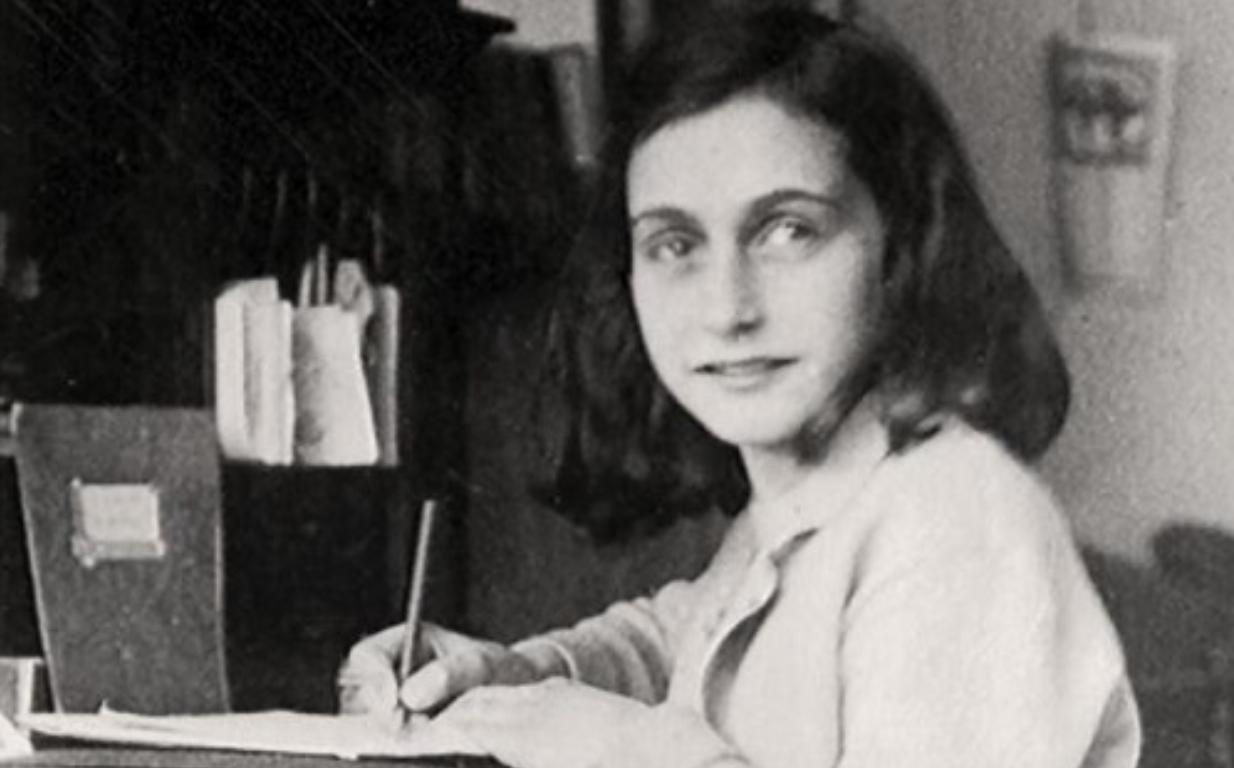 La imagen muestra a Ana Frank escribiendo su diario.