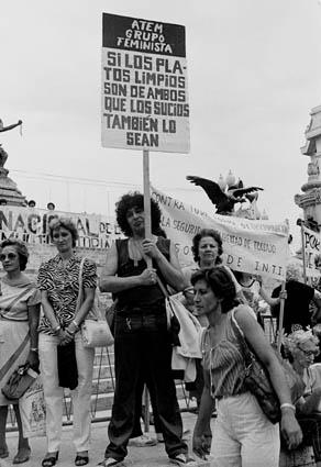 Fotografía en blanco y negro de un grupo de mujeres sosteniendo carteles. De fondo el edificio del Congreso de la Nación y más pancartas. En el centro, una mujer levanta un cartel con el texto: Si los platos limpios son de ambos, que los sucios también lo sean.