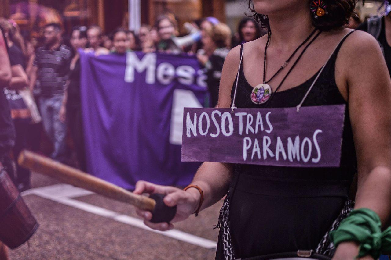 Fotografía color tomada durante una marcha por el 8M. Se ven personas fuera de foco al fondo y en primer plano una mujer que lleva colgado al cuello un cartel con el mensaje: nosotras paramos.
